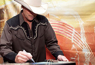 Alan Jackson signing the Tomkins guitar